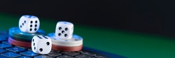 Online gaming platform, casino and gambling business. Casino dice and chips on laptop keyboard on green background.