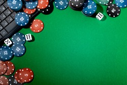 Online gaming platform, casino and gambling business. Dice and multi-colored game pieces on a laptop keyboard on a green background.