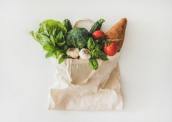 Online grocery healthy shopping. Flat-lay of fruit, vegetables, greens and bread in eco-friendly bag over white background, top view. Shop online during pandemic of coronavirus banner for website