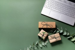 Online holiday shopping concept. Lap top, gift boxes and eucalyptus twigs on deep green background.