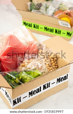 Online Home Food Delivery. Craft Box with packed tuna, shrimp, vegetables and recipe card on a kitchen background. Food delivery services during coronavirus pandemic and social distancing Photo stock ©