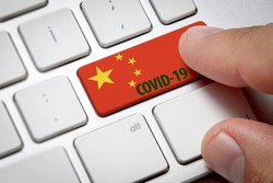Online international business concept: computer key with China.Male hand searching information about Covid-19 by pressing computer key with Chinese flag