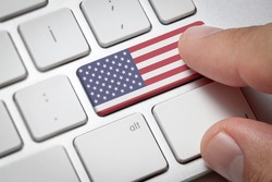 Online International Business concept: Computer key with the United States of America flag on it. Male hand pressing computer key with America flag.