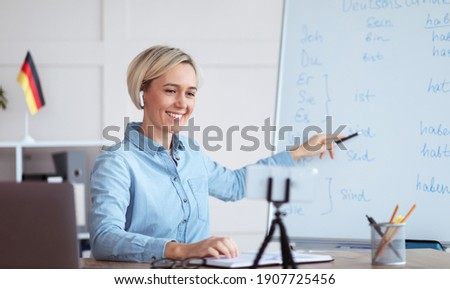 Online languages school. Millennial female tutor giving German lesson on internet, using smartphone, pointing at blackboard, explaining grammar to remote students. Education during covid-19 epidemic ストックフォト ©