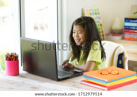 Online learning student.Girl e-learning.Young child homeschooling during corona virus pendemic. Kid home education.Schooling at home.Asian school girl on wireless laptop.Homeschool.Lockdown.