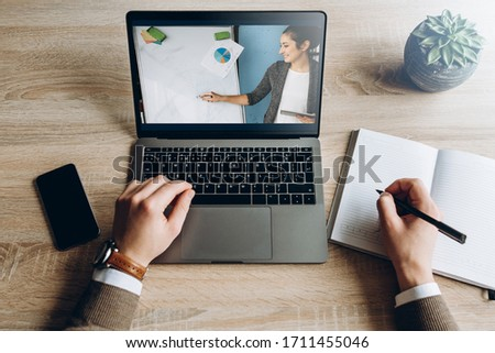 Online learning using a laptop. A student is studying online via video communication while sitting at a table. Young girl teacher shows information on a board