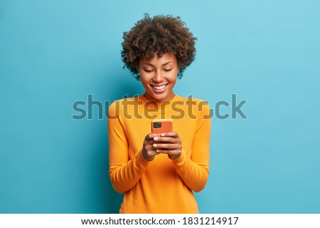 Online lifestyle concept. Cheerful good looking woman with Afro hair sends text messages via mobile phone dressed casually searches gifts for holiday in internet uses smartphone app browses webpage Photo stock ©
