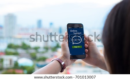 Online Live chat support concept.close-up of female hands holding mobile phone on blurred urban city as background