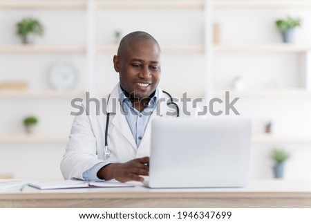 Online medical consultation. Highly qualified black doctor consultating patients distantly from his office during quarantine, using laptop computer, typing diagnosis and sending emails