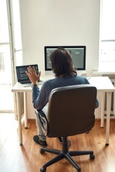 Online meeting with colleagues. Back view of male web developer looking at webcam and waving while sitting at his workplace and working from home, writing code. Freelance. Stay home, self isolation
