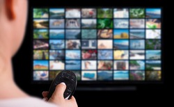 Online Multimedia video concept on TV set in dark room. Woman watching online TV with remote control in hand. Multimedia streaming VoD content provider concept.