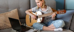 Online music learning. Girl playing acoustic guitar and watching online course on laptop while lesson at home. Online training, online classes. Remote training. education