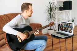 Online musical performance. A young guy sits on the sofa at home and plays acoustic guitar in front of online audience on the laptop screen. Video concert online, video chat