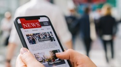 Online news on a mobile phone. Close up of businesswoman reading news or articles in a smartphone screen application. Hand holding smart device. Mockup website. Newspaper and portal on internet.