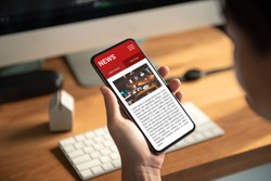 Online news on a smartphone. Mockup website. Woman reading news or articles in a mobile phone screen application at home. Newspaper and portal on internet.