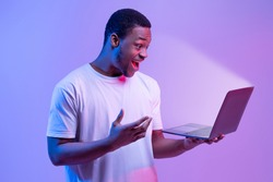 Online Offer. Surprised African American Man Holding Laptop Looking At Glowing Screen, Excited Black Guy Playing Games Or Browsing Internet On Computer, Stranding In Neon Light Over Purple Background