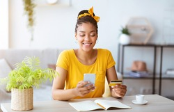 Online Order And Ecommerce Concept. Smiling African American Woman Using Smartphone And Holding Credit Card, Sitting At Desk With Open Notebook In Living Room At Home. Internet Shop Offers And Sales