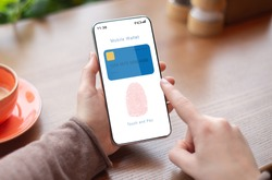 Online Payment And Biometric Identification Concept. Over The Shoulder View Of Person Holding Smartphone In Hand Showing Mobile Wallet App With Fingerprint Icon On Device Screen For Scanning