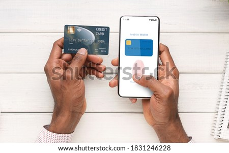 Online Payment And Biometric Identification Concept. Top Above View Of Black Man Holding Cellphone And Credit Card In Hand Showing Mobile Wallet App With Fingerprint Icon On Screen For Scanning Stockfoto ©
