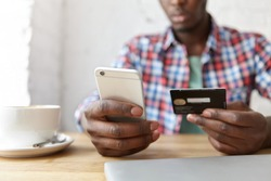 Online payment and shopping. Cropped portrait of African man in plaid shirt holding cell phone in one hand and debit card in other, paying bill at cafe, using mobile banking application during lunch