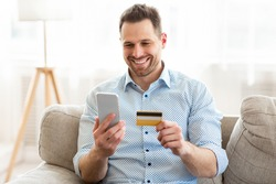 Online Payment. Frontal portrait of man holding debit card and using smartphone for shopping at home, copy space