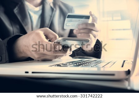 Online payment,Man's hands holding a credit card and using smart phone for online shopping  #331742222