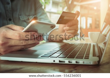 Online payment,Man's hands holding smartphone  and using credit card for online shopping. #556236001