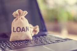 Online personal loan, financial concept : Loan bags on a laptop, depicting peer-to-peer lending, the practice of lending money to individual or business via online service among lenders and borrowers