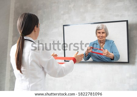Online physiotherapy for the elderly. Doctor showing an elderly woman exercises with a fitness rubber band. Remote medicine during quarantine. Female doctor consults on video conference.