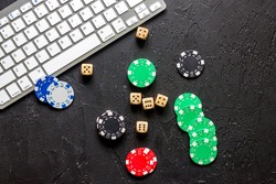 Online poker. Chips and the dice nearby keyboard on grey stone table top view copyspace