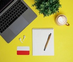 online Polish language courses. Layout of laptop, headphones, Polish flag, notepad with pen, cappuccino coffee and plant on yellow background