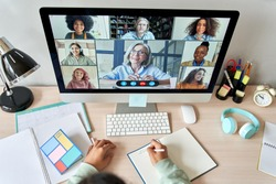 Online remote high school class concept. Mixed race college student distance learning at home on desk using computer conferencing with teacher and classmates group virtual meeting on screen. Top view