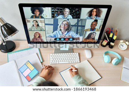 Online remote high school class concept. Mixed race college student distance learning at home on desk using computer conferencing with teacher and classmates group virtual meeting on screen. Top view Сток-фото ©