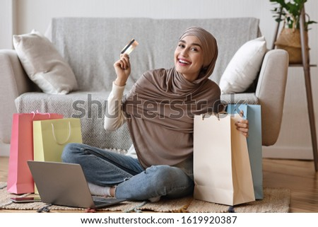 Online Sales. Arabic Girl In Hijab Happy After Successful Internet Shopping, Sitting On Floor With Shopper Bags, Laptop And Credit Card