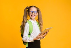 Online School. Happy Schoolgirl Holding Digital Tablet Recommending Educational App For Distant Learning Posing Over Yellow Studio Background.