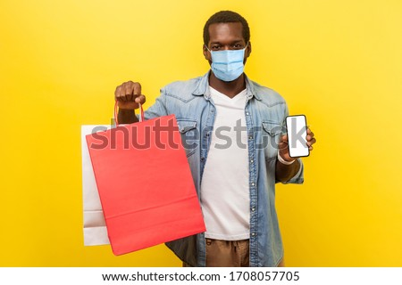Online shopping and delivery on quarantine. Portrait of young man with medical mask holding packages and showing smartphone and looking with smile. indoor studio shot isolated on yellow background