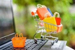 Online shopping and e commerce with delivery service concept : Plastic shopping basket on laptop with trolley / cart and paper shopping bags behind. Online shopping is popular due to its convenience.