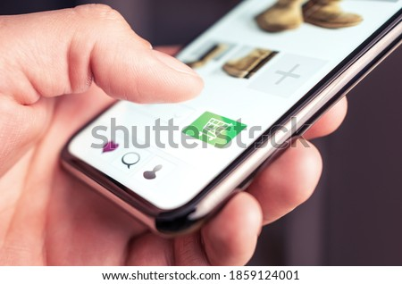 Online shopping and fashion store website with add to cart button in mobile phone. Customer order and purchase product on internet site. Ecommerce and retail business concept. Digital transaction.