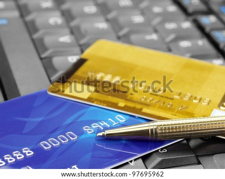 Online shopping. Closeup of credit cards and pen on computer keyboard