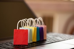 Online shopping concept: colorful paper shopping bags on notebook keyboard. E-commerce is the purchase of products and services on the internet can purchase goods or services foreign country.