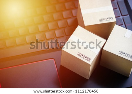 Online shopping concept e-commerce delivery buying service. square cartons shopping on laptop keyboard, showing customer order via the internet.
