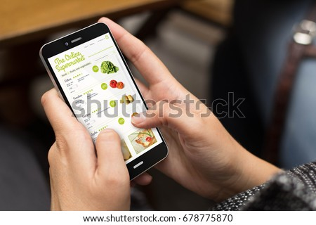 online shopping concept: girl using a digital generated phone with online supermarket on the screen. All screen graphics are made up.