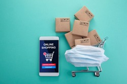 Online shopping concept. Smart phone with shopping cart on mint background. Home quarantine. Top view.