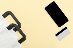Online shopping concept. Top view of white paper shopping bags, phone and credit card on yellow background