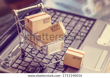 Online shopping / e-commerce and customer experience concept : Boxes with shopping cart on a laptop computer keyboard, depicts consumers / buyers buy or purchase goods and service from home or office Stockfoto ©