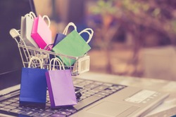 Online shopping  e-commerce and customer experience concept : Shopping bags and a shopping cart on a laptop keyboard, depicts consumers  buyers buy or purchase goods and service from home or office