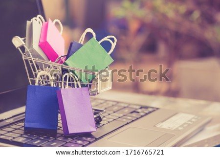 Online shopping / e-commerce and customer experience concept : Shopping bags and a shopping cart on a laptop keyboard, depicts consumers / buyers buy or purchase goods and service from home or office