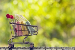 Online shopping, e-commerce concept: Paper shopping bags in a trolley or shopping cart  in the natural green background. purchase of products on internet can purchase goods from foreign countries