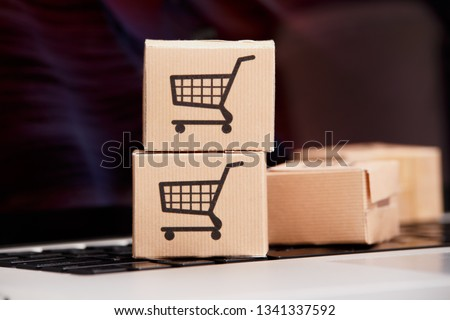 Online shopping . ecommerce and delivery service concept : Paper cartons with a cart or trolley logo on a laptop keyboard, depicts customers order things from retailer sites via the