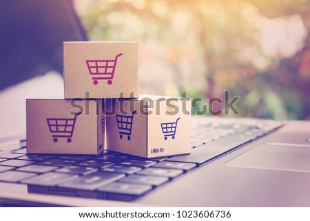 Online shopping / ecommerce and delivery service concept : Paper cartons with a shopping cart or trolley logo on a laptop keyboard, depicts customers order things from retailer sites via the internet. Stockfoto ©